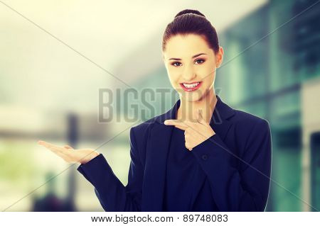 Young happy businesswoman showing copyspace