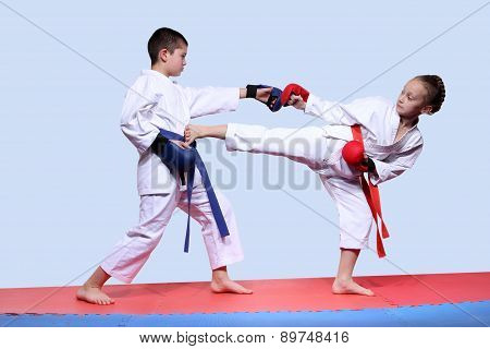 Children in karategi are beating kicking and punching