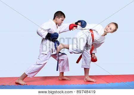 On the red and blue mats athletes  are doing paired exercises karate