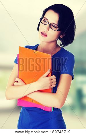 Worried young woman holding documents