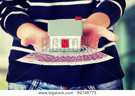 Happy woman holding a house model