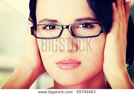 Closeup of frustrated young woman holding her ears.