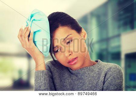Woman with ice bag having headache.