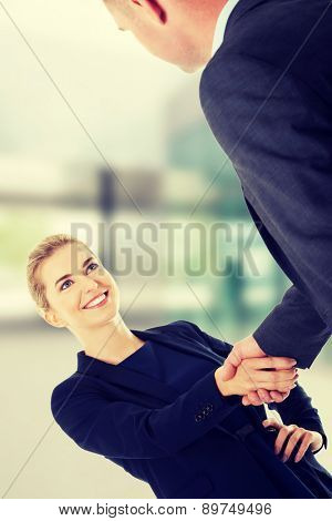 Happy business couple shaking hands
