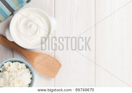 Dairy products on wooden table. Sour cream and curd. Top view with copy space