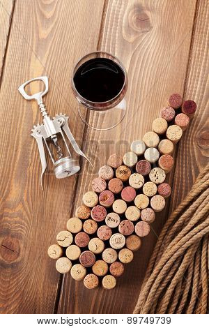 Wine bottle shaped corks, glass of red wine and corkscrew over rustic wooden table background. Top view
