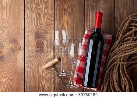 Red wine bottle, glasses and corkscrew over rustic wooden table background with copy space