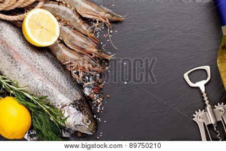 Fresh raw sea food with spices and whtie wine bottle on black stone background. Top view with copy space