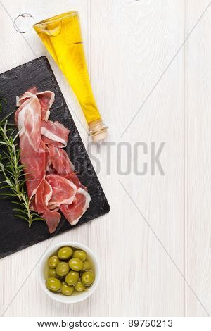 Prosciutto with rosemary, olives and olive oil on wooden table. Top view with copy space