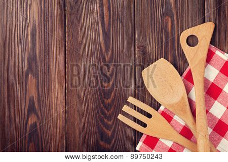 Kitchen cooking utensils over wooden table background. Top view with copy space. Retro toned