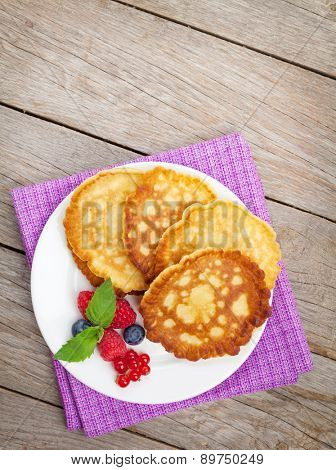 Pancakes with raspberry and blueberry. On wooden table background with copy space