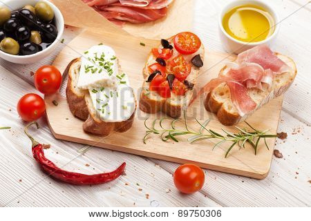 Bruschetta with cheese, tomatoes and prosciutto on cutting board