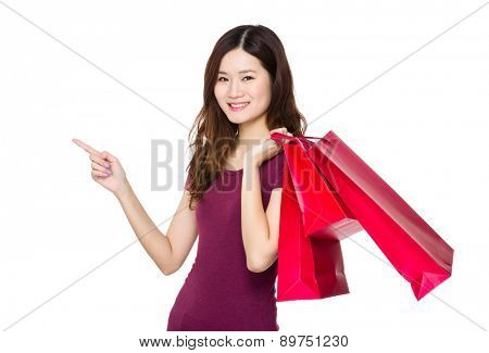 Young woman hold with shopping bag and finger point upwards