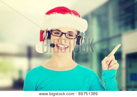 Young casual woman in santa hat and,microphone and headphones