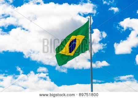 Brazilian waving flag on blue sky