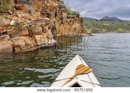 canoe and sandstone cliff - springtime paddling Horsetooth Reservoir near Fort Collins, Colorado