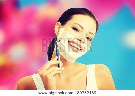 Young happy woman shaving face