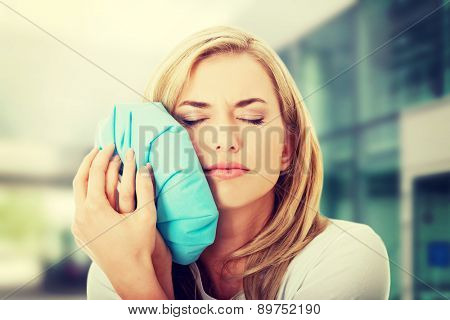 Woman with tooth ache holding an ice bag near her face