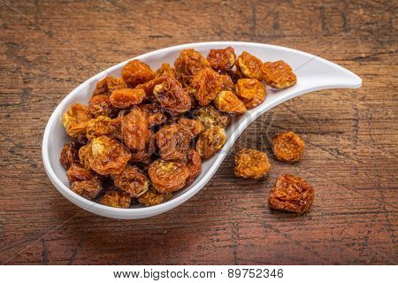 dried goldenberries in a ceramic teardrop shaped bowl against rustic scratched wood