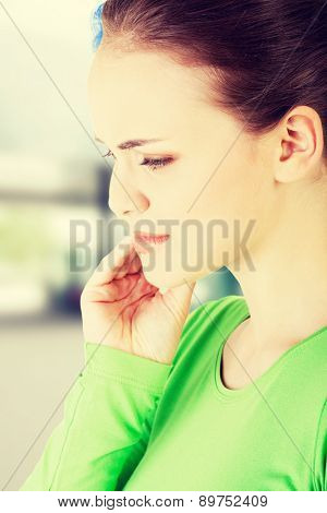 Teen woman pressing her bruised cheek with a painful expression