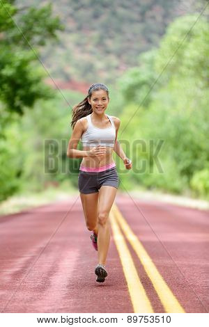 Runner woman running training living healthy fitness sport lifestyle. Active female athlete jogging outdoors happy with aspirations. Beautiful mixed race Asian Caucasian girl in full body length.
