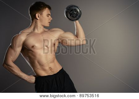 Athlete man doing exercises with dumbbells. Bodybuilding. Muscles of the arms. Studio shot.