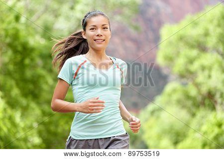 Woman runner running training living healthy fitness sport lifestyle. Active female athlete jogging outside smiling happy with aspirations. Beautiful young mixed race Asian Caucasian girl in her 20s.