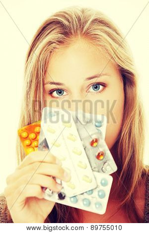 Young beautiful woman holding pills