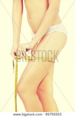 Young slim woman measuring her thigh