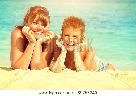 Mother and Son having fun at the beach. Travel and Vacation concept. Happy Mom with Little Child Having Fun outdoors. Joyful Family. Summer Holidays