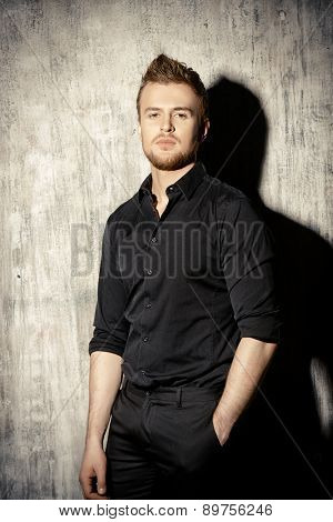 Fashionable man in black shirt posing at studio. Men's beauty, fashion.