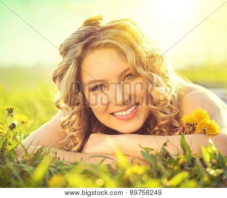 Beautiful Young Woman lying on a field, green grass and dandelion flowers. Outdoors Enjoy Nature. Healthy Smiling Girl lying in Green Grass