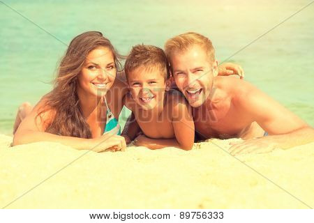 Happy Young Family with Little Kid Having Fun at the Beach. Joyful Family. Travel and Vacation. Summer Vacations. Seaside