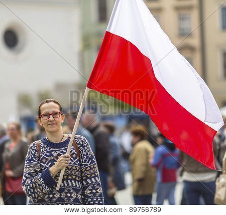 Young woman on the street holding a Polish flag.