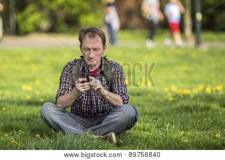 Young man with smartphone sitting on the grass in a city Park.