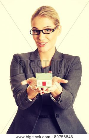 Businesswoman holding a house model.