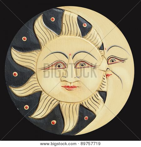 Sun and moon profiles, ancient carved wooden, isolated on a black background
