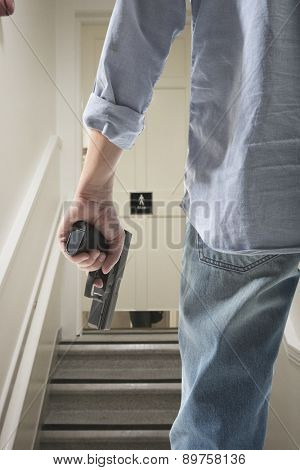 Bodyguard with gun protects client against an s water closet door background
