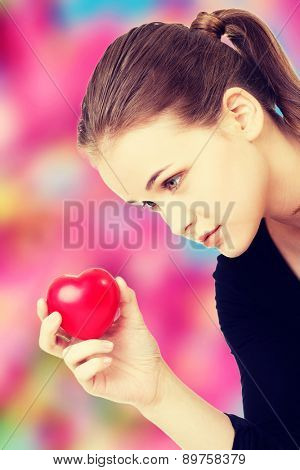 Young beautiful woman holding heart