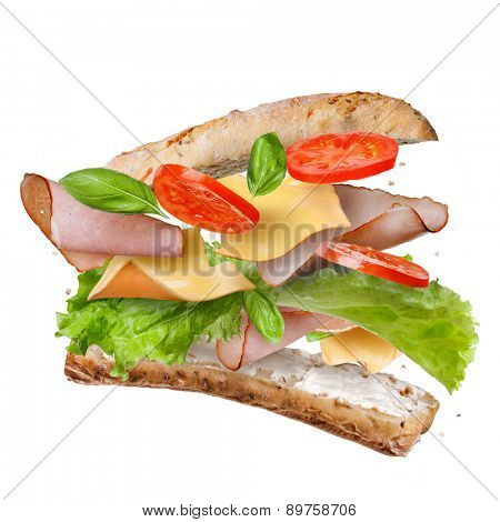 Sandwich with falling ingredients in the air isolated on white - slices of fresh tomatoes, ham, cheese and lettuce