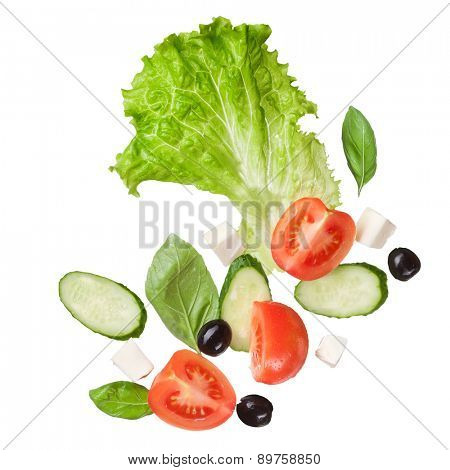 falling salad isolated in white - red tomatoes, pepper, cheese, basil, cucumber and olives