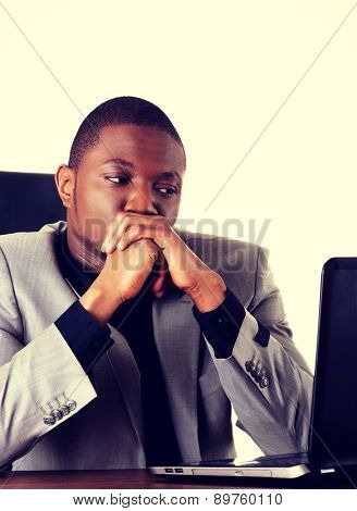 Black man sitting with the laptop on desk