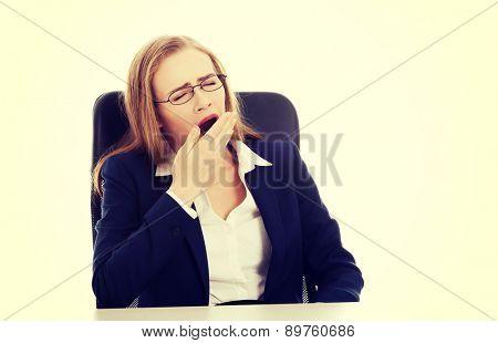 Beautiful businesswoman in glasses yawning