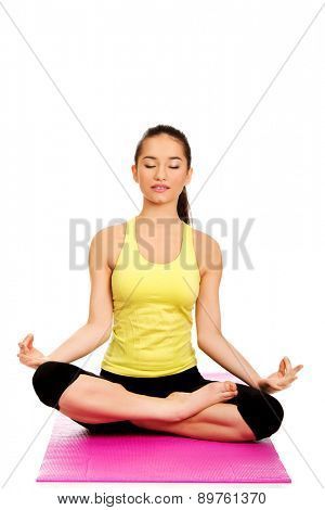 Attractive young woman meditating in pose of lotus.