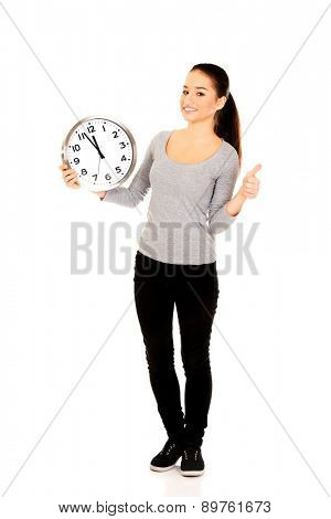 Happy woman with a clock and thumbs up.