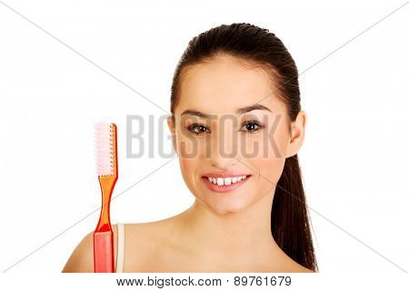 Young beautiful woman holding big toothbrush and smiling.