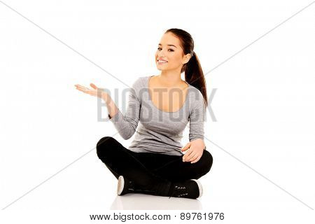 Young woman sitting cross legged with open hand.
