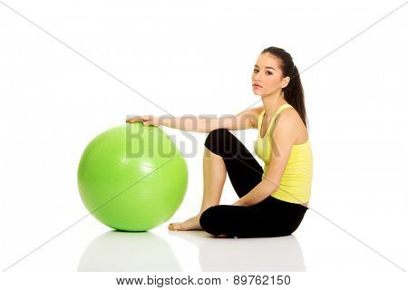 Young fitness woman relaxing with pilates ball.