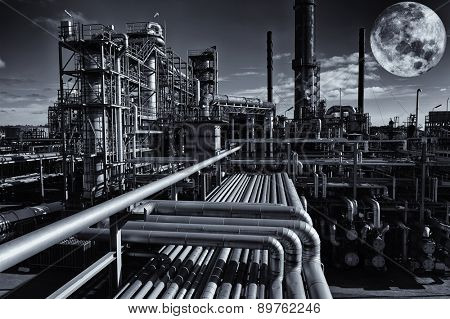 oil and gas refinery under a large full moon, night-time image