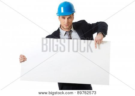 Handsome businessman in hard hat holding empty banner.